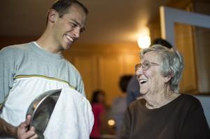 Ein junger Mann hilft einer älteren Dame beim Abwasch. Für geistiges Wachstum ist der Dienst am Nächsten unerlässlich.