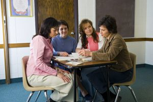 """Eine Präsidentschaft der """"Jungen Damen"""" sitzt gemeinsam an einem Tisch, um zu planen."""