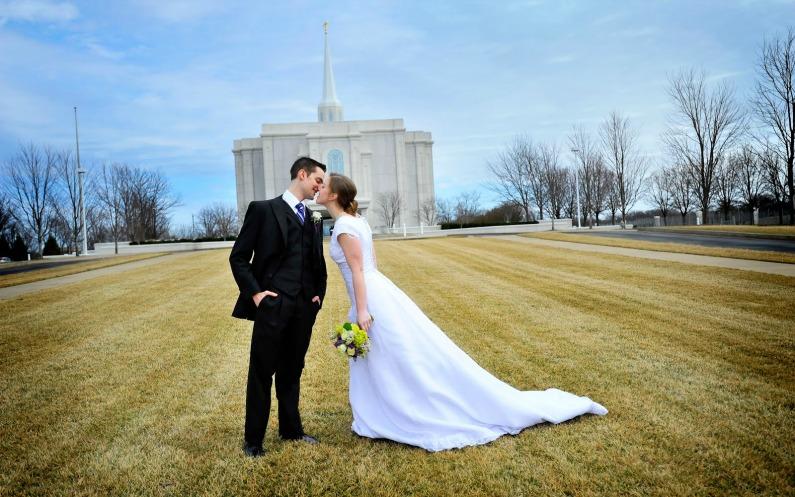 Ein gerade aneinander gesiegeltes Ehepaar küsst sich, im Hintergrund ist ein Tempel der Mormonen zu sehen.