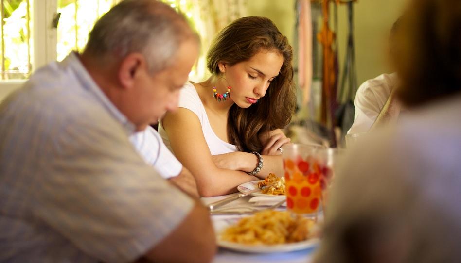 Familie dankt Gott für ihre Mahlzeit.