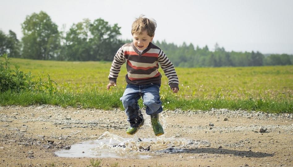 Junge springt in einer Pfütze