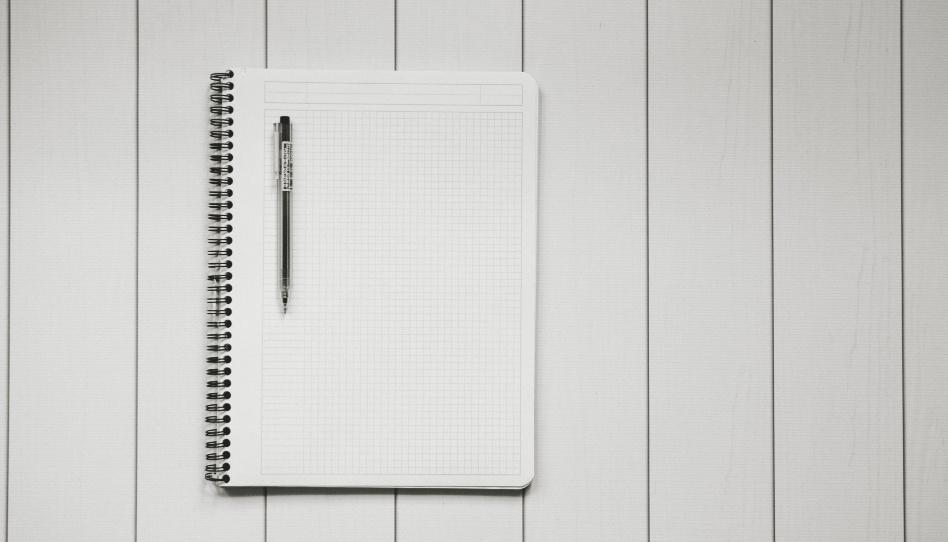 Zu sehen ist ein Notizbuch auf welchem ein Stift liegt. Damit könnte man beispielsweise einen Haushaltsplan festhalten.