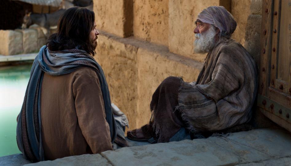 Jesus Christus sitzt neben einem kranken, älteren Mann auf einer Treppenstufe.