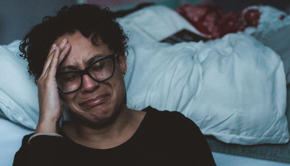 Eine Frau sitzt vor ihrem Bett auf dem Boden und weint. So brechen leider auch viele Opfer von Missbrauch immer wieder unter Tränen zusammen.