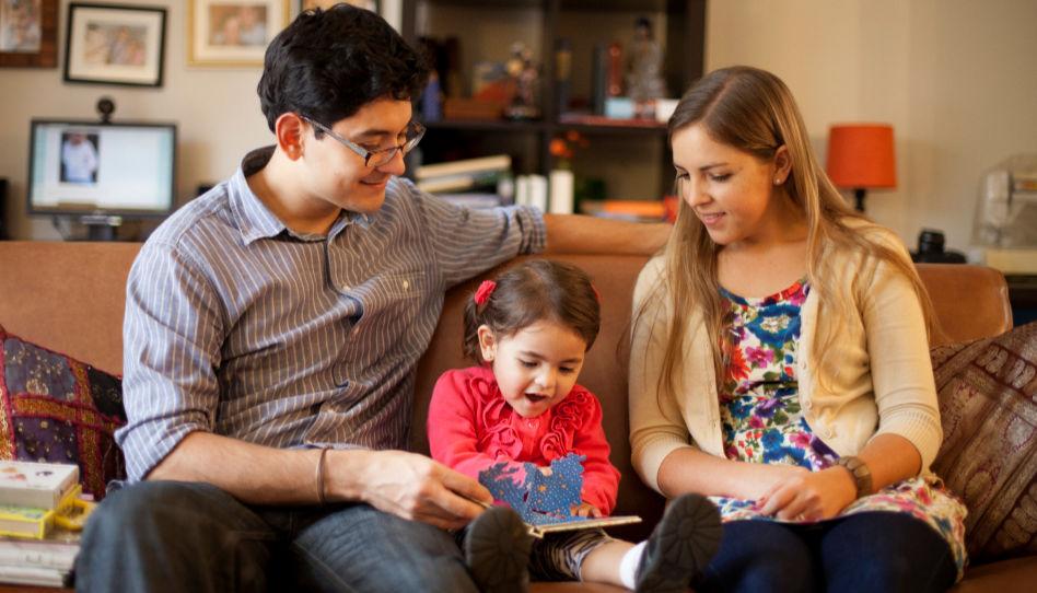 Eltern schauen mit ihrer Tochter in ein Kinderbuch.