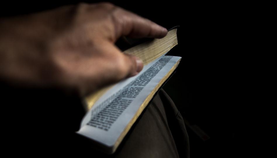 Zu sehen ist eine Hand, die die Heiligen Schriften öffnet. Wenn wir vom Chaos des Alltags um uns herum mal entfliehen möchten und uns nach etwas Frieden sehnen, können wir sie zum Beispiel in der Bibel oder dem Buch Mormon finden.