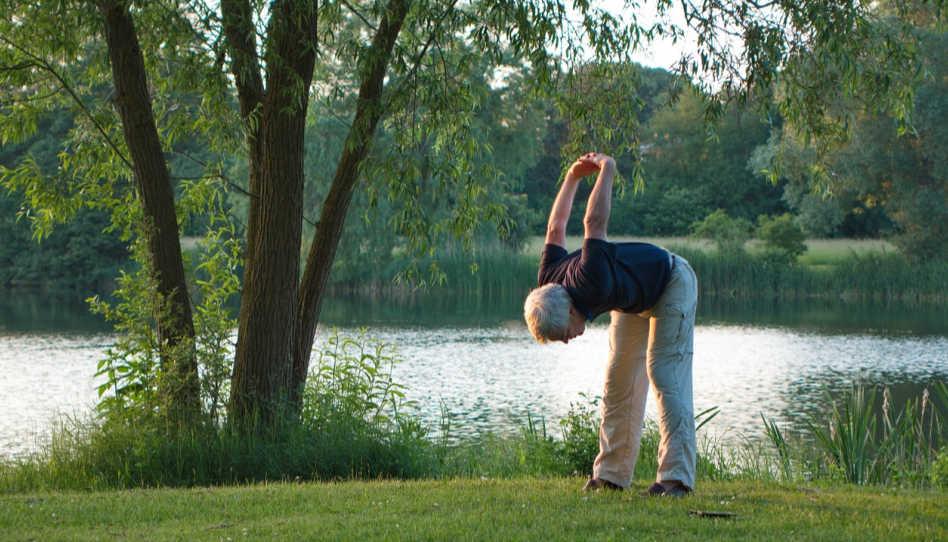 Jemand macht Yoga-Übungen an einem See. Wir sollen auch in geistiger Hinsicht in Bewegung bleiben, um uns vor dem Stillstand zu bewahren, der durch den Einfluss des Satan kommen entstehen kann.