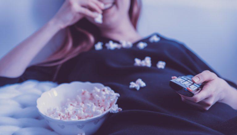 Eine Frau liegt lachend auf der Couch und isst Popcorn. Auch wir können, trotz Chaos im Haushalt, Spaß und Freude am Leben haben. Das allerwichtigste ist und bleibt unsere Familie.