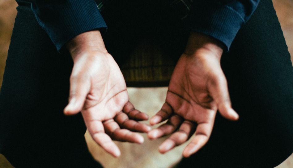 Zu sehen sind die Innenseiten der Hände eines Mannes., der auf einer Couch sitzt. Opfern von Misshandlungen wird empfohlen, mit einem Therapeuten zu sprechen.