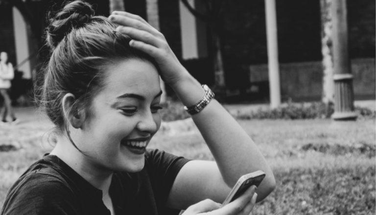 Zu sehen ist eine junge Frau, die überrascht auf ihr Handy schaut.