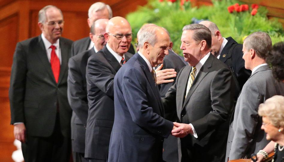 Zu sehen sind Präsident Nelson, Präsident Oaks, Elder Holland und andere Generalautoritäten der Kirche Jesu Christi, die sich brüderlich zu Beginn einer Generalkonferenz begrüßen.