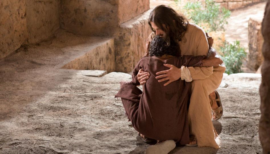 Zu sehen ist Jesus Christus, der einen Mann auf dem Boden sitzend umarmt. Christus hat seine Lehre, nämlich andere zu lieben, immer in Perfektion vorgelebt.