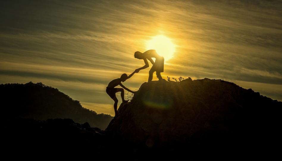 Zu sehen sind zwei Jugendliche. Einer der beiden hilft dem anderen einen Berg hoch. So stehen uns in unserem Leben auch Engel zur Seite, manchmal, ohne es zu wissen.