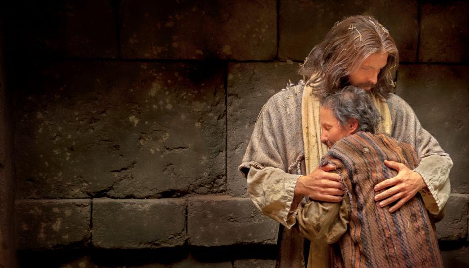 Jesus Christus drückt liebevoll eine ältere Frau an sich.