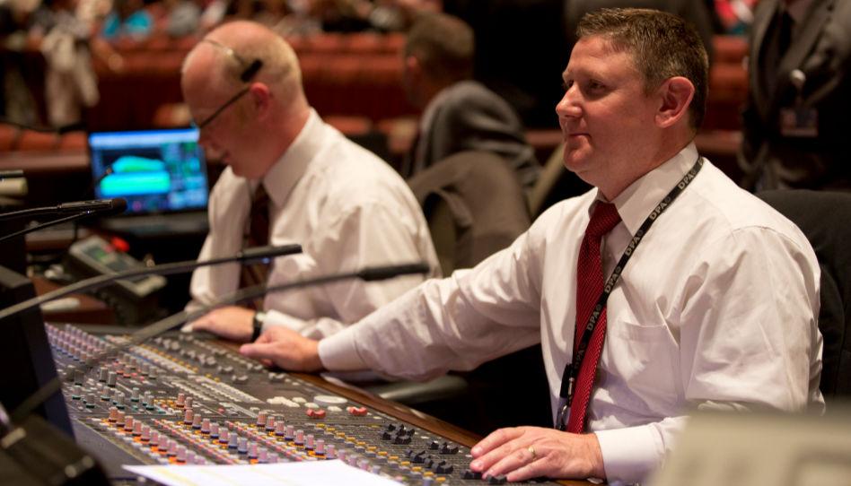 Zu sehen sind zwei Männer die während einer Generalkonferenz für einen Teil der Technik zuständig sind.