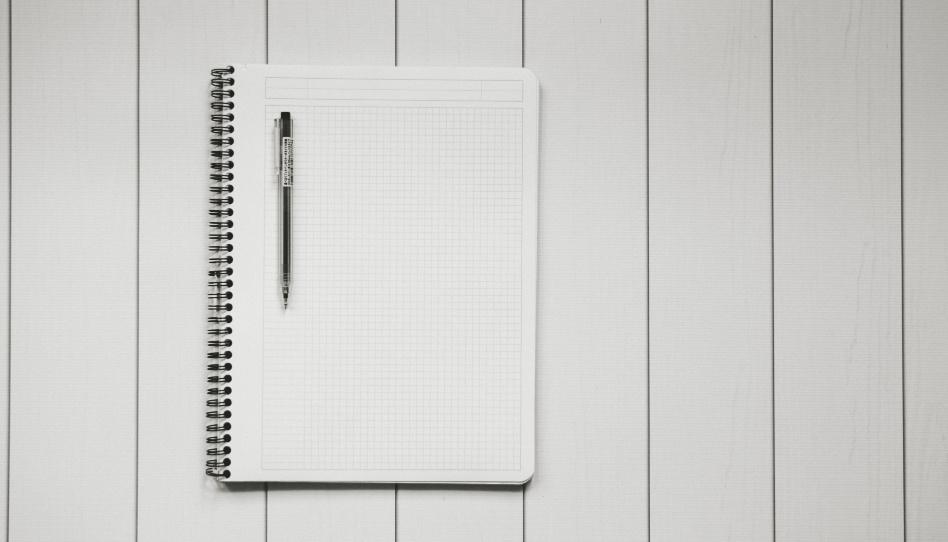 Zu sehen ist ein geöffnetes Ringbuch auf welchem ein Stift liegt. In Bezug auf die Lehre entscheiden wir, ob wir sie anwenden und dadurch Seiten unseres Buches füllen, oder ob die Seiten unberührt und weiß bleiben.