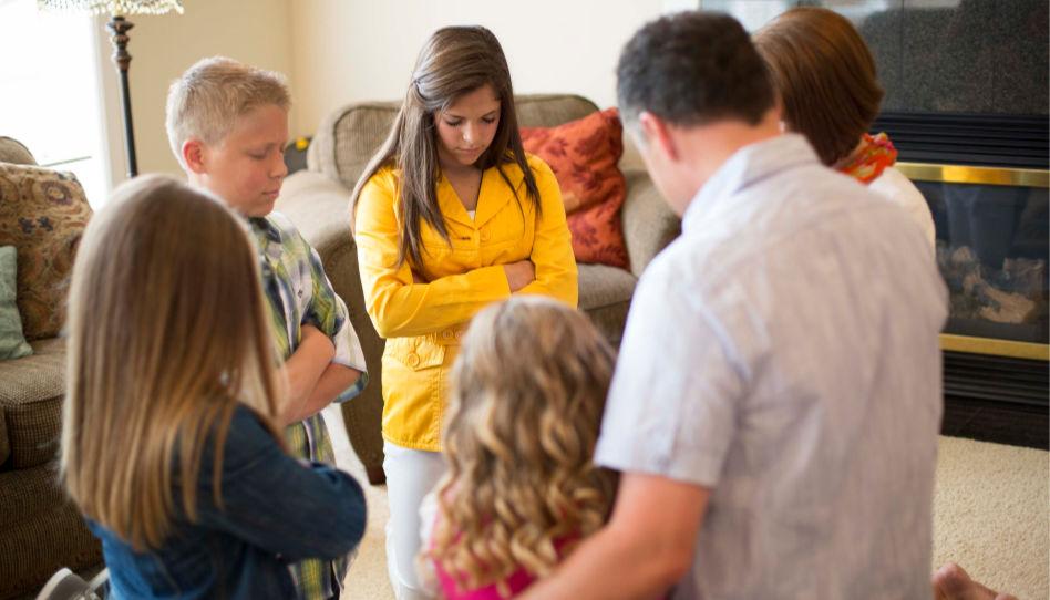 Zu sehen ist eine Familie, die auf dem Boden kniend miteinander betet. Das ist ein tolles Beispiel für gelebte Lehre.