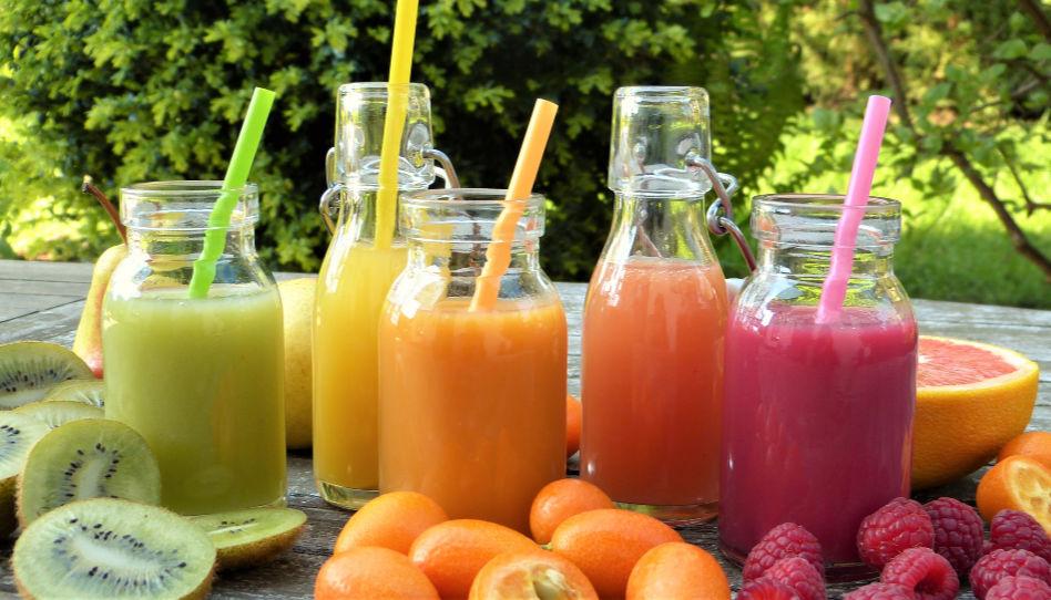 Zu sehen sind vitaminhaltige Smoothies und das zugehörige Obst.