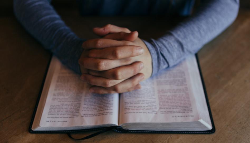 Zu sehen sind zum Gebet gefaltete Hände auf einer Bibel. In Vorbereitung auf die Generalkonferenz können wir um Inspiration bitten und uns Fragen notieren, die wichtig für unser Leben sind.