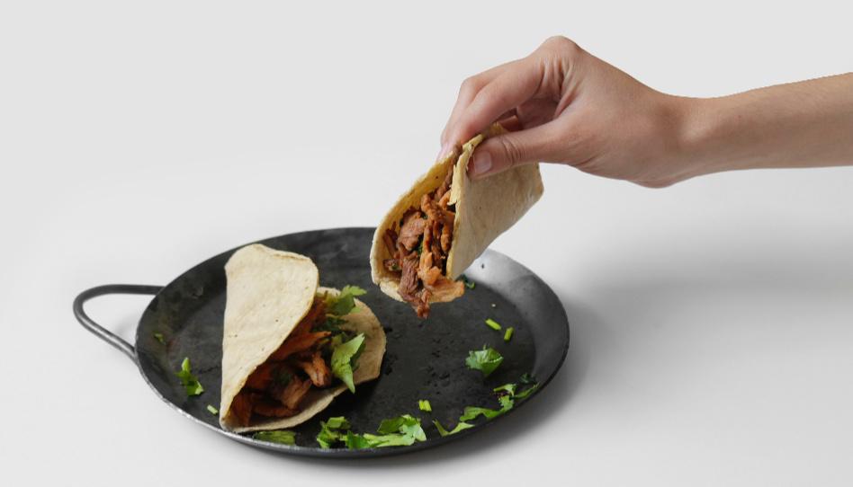 Zu sehen ist eine Hand, die einen gefüllten Tortilla-Wrap aus einer Pfanne nimmt. Unser erstes Rezept für die Osterzeit ist eines für Tortilla-Wraps.