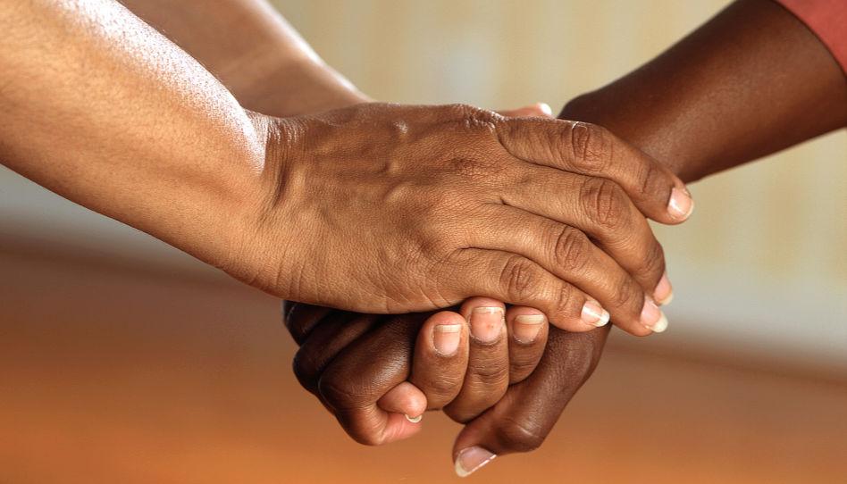 Zu sehen sind zwei Hände, die eine dritte Hand tröstend umschließen.