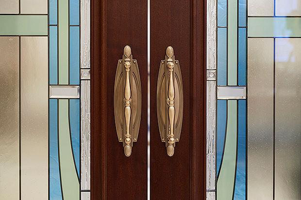 Zu sehen sind zwei Fenstergriffe und außen herum weitere Glasmalereien.