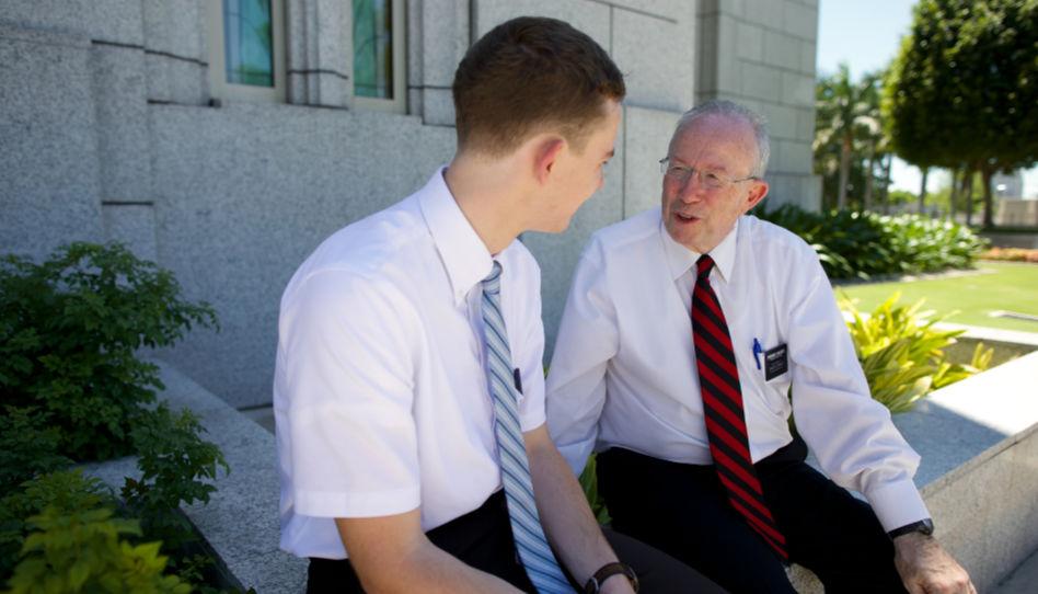 Zu sehen sind ein älterer Herr (Missionar) und ein junger Mann. Sie sitzen auf der Mauer eines Tempels und unterhalten sich.