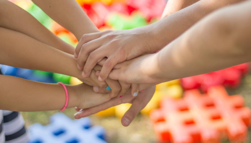 Zu sehen sind mehrere aufeinandergelegte Hände, zum Zeichen von Freundschaft und Zusammenhalt. Eine tiefe Freundschaft kann den Blick auf psychische Krankheiten beiderseits verändern, und zwar positiv.