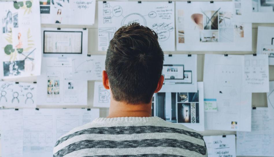 Zu sehen ist ein Mann von hinten, der sich eine Wand voller Zettel anschaut. So bereiten sich manche auf eine Prüfung vor.