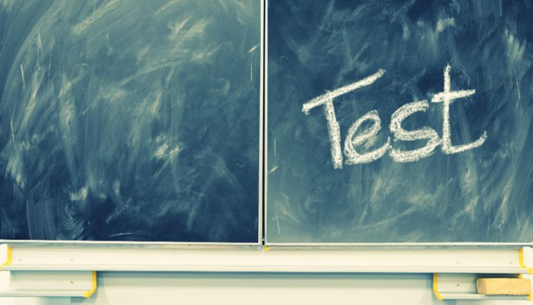 """Zu sehen ist eine Tafel. Auf der rechten Seite ist mit Kreide das Wort """"Test"""" geschrieben."""
