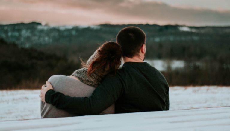 Zu sehen ist ein Paar welches auf einer Bank sitzt. Man sieht sie von hinten. Für viele Paare ist die (vorübergehende) Kinderlosigkeit ein Thema, dass zu Trauer und Tränen führt.