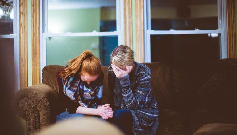 Zu sehen sind zweiweinende Frauen. Eine der beiden hält die Hand der anderen. Viele Personen die kinderlos sind, vergießen Tränen der Trauer und der Verzweiflung.