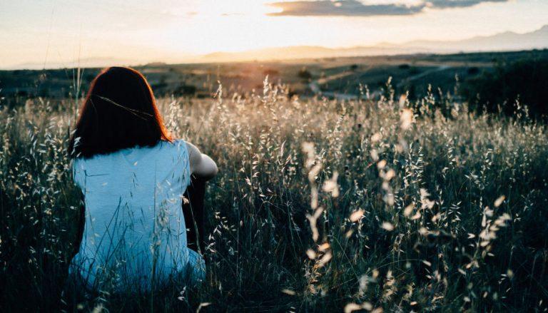 Zu sehen ist der Rücken einer Frau, die auf einer Wiese sitzt und in Richtung Horizont schaut. Diese Frau steht symbolisch für Menschen, die voller Hoffnung oder aber auch Trauer in die Zukunft oder auf den Herrn schauen. Auch hier in Deutschland gibt es viele ungewollt kinderlosen Paare.