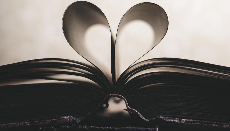 """Zu sehen ist ein geöffnetes Buch. Einige Seiten sind so nach innen gafaltet, dass sie ein Herz ergeben. In Zeiten der """"Prüfung"""" können wir uns durch das Lesen heiliger Schrift, das Gebet oder Fasten an den Herrn wenden."""