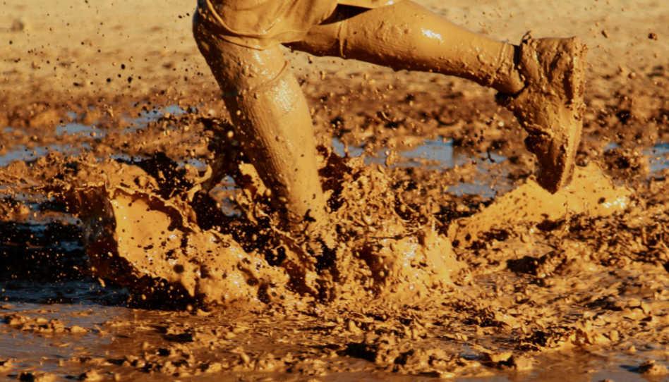 Auf diesem Bild sieht man die Beine eines Mannes, der durch tiefen Schlamm läuft. Er befindet sich auf einem schwierigen Weg.