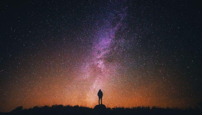 Zu sehen ist eine Frau, die in einen wundervollen Sternenhimmel schaut. Wie ein Sternenhimmel, wird aus verschiedenen Offenbarungen ein vollkommenes Bild des Evangeliums Jesu Christi.
