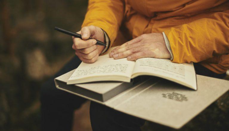 Zu sehen ist jemand, der in ein Tagebuch schreibt. Seine Gedanken in einem Tagebuch festzuhalten kann zu persönlicher Offenbarung führen.