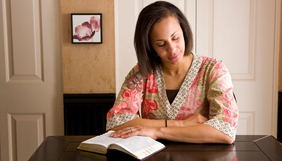 Zu sehen ist eine Frau, die in den heiligen Schriften liest.
