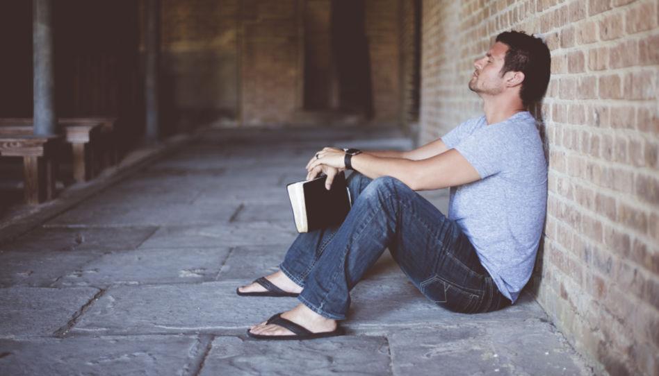 Zu sehen ist ein Mann der auf dem Boden sitzt, eine Bibel in der Hand hat und nach oben schaut.