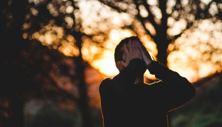 Zu sehen ist ein Mann, der sich die Hände vor das Gesicht hält. Dies soll eine Darstellung eines Menschen sein, welcher wütend auf Gott ist.