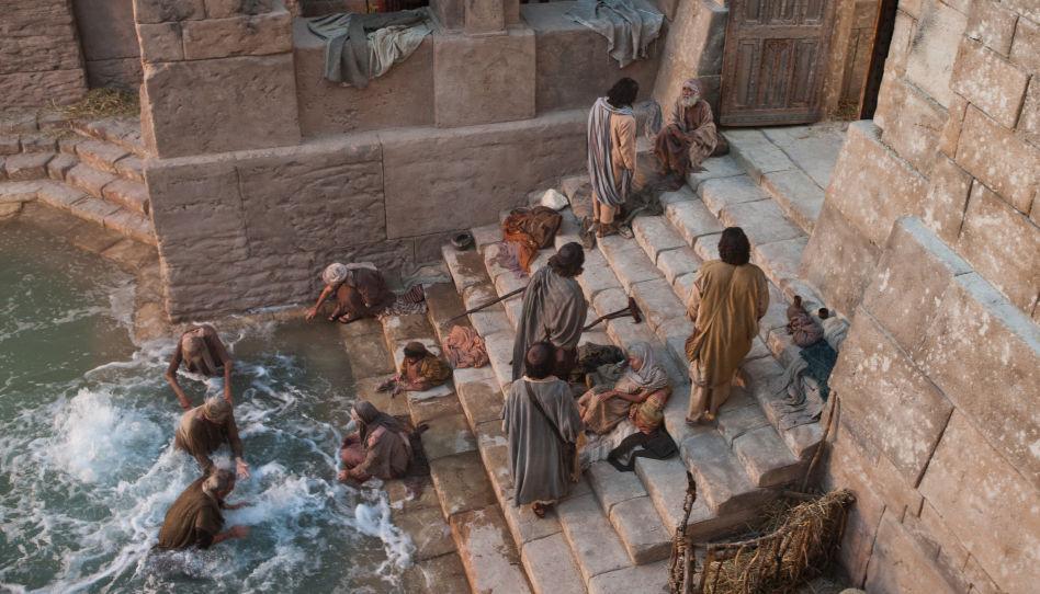 Jesus spricht mit einem älteren Herrn, der auf einer Stufe sitzt, während sich weiter unten mehrere Männer im Wasser waschen.