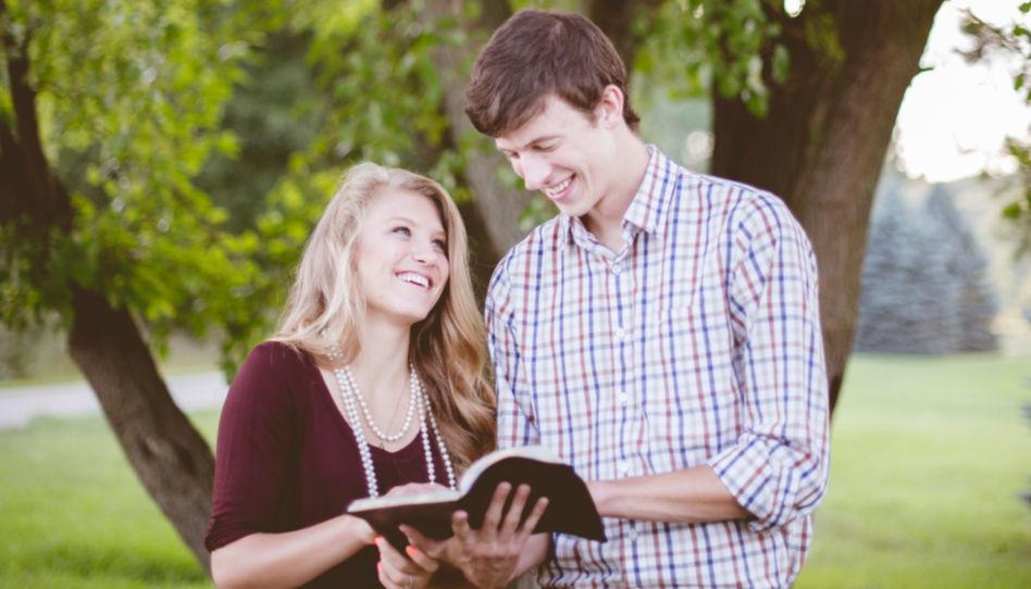 Zu sehen ist ein Pärchen, das lächelnd in der Bibel liest.