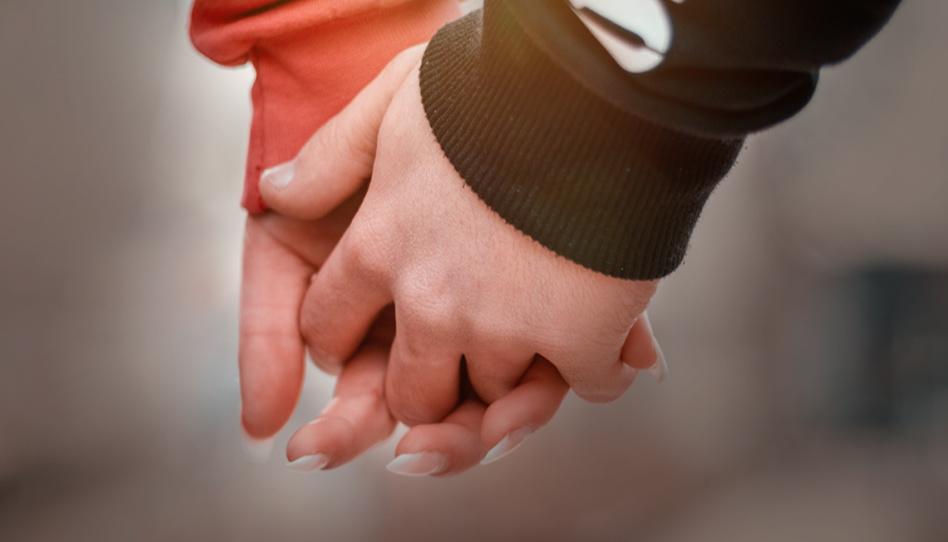 Zu sehen sind die Hände eines Pärchens, das Händchen hält.