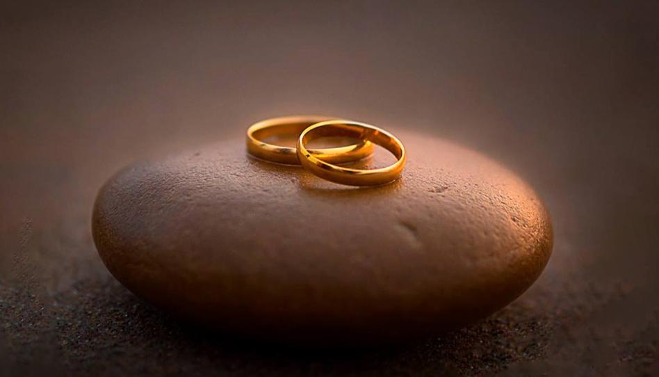 Auf diesem Foto sind zwei goldene Eheringe, auf einem Stein liegend, zu sehen