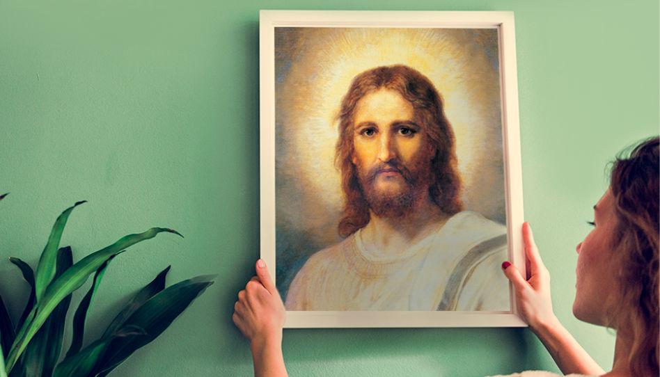 Hier ist eine junge Frau zu sehen, die ein Bild von Jesus Christus aufhängt.
