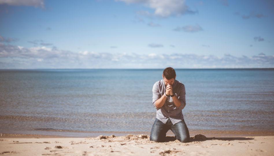 Ein Mann kniet an einem Strand und betet.