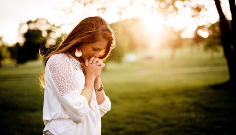 """Da das Thema dieses Beitrags """"Beten lernen"""" ist, sieht man auf diesem Bild eine junge Frau, die auf einem Rasen kniet und betet."""