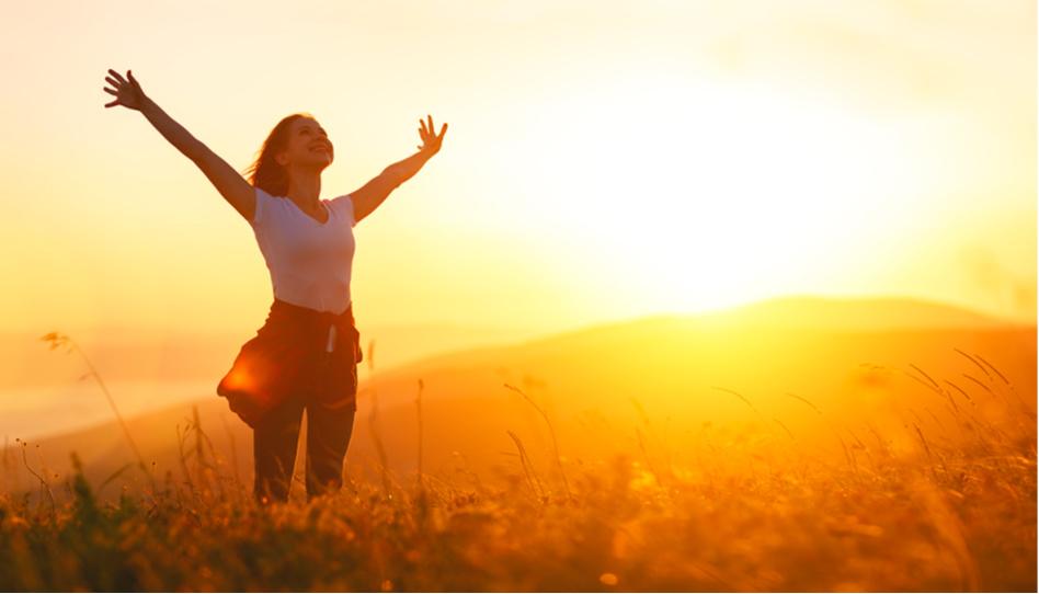 Zu sehen ist eine junge Frau die freudestrahlend, mit beiden Armen in die Luft gestreckt gen Himmel schaut.