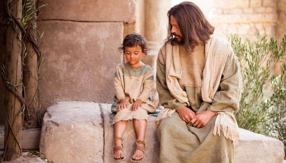 Jesus sitzt neben einem Kind und spricht mit ihm.