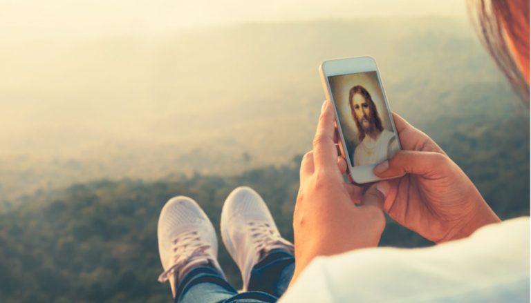 Der Beitrag behandelt die Frage, wie es wohl wäre, Jesus zu begegnen. Darum ist auf dem Bild eine junge Frau zu sehen (von hinten), die auf ein Christusbild in ihrem Handy schaut.